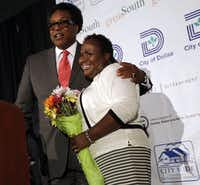 "In June 2014, Dallas City Council member Dwaine Caraway presented a bouquet of flowers to fellow council member Carolyn Davis, whom he referred to as ""his little fireball,"" and thanked her for her help getting an apartment complex project completed in his district. That was the Lancaster Urban Village.(Mona Reeder/Staff Photographer)"