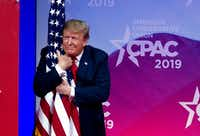 President Donald Trump hugs the American flag as he arrives on stage to speak at the Conservative Political Action Conference, CPAC 2019, in Oxon Hill, Md., on March 2, 2019.(Jose Luis Magana/AP)