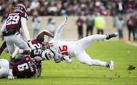 Texas A&M Aggies linebacker Tyrel Dodson (25) and defensive back Donovan Wilson (6) tackle Ole Miss Landsharks defensive back Myles Hartsfield (15) during the first quarter of a college football game between Texas A&M and Ole Miss on November 9, 2018 at Kyle Field in College Station, Texas. (Ashley Landis/Staff Photographer)