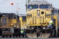 A train operator (left) dismounts a Union Pacific locomotive while another operator climbs up at a railyard in Council Bluffs, Iowa.(Nati Harnik/The AP)