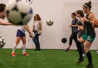 Director Wendy Dann walks by as the cast practices their soccer skills during a rehearsal for&nbsp;<i>The Wolves </i>at Wyly Theatre in Dallas.(Shaban Athuman/Staff Photographer)
