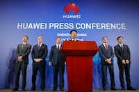 Huawei Rotating Chairman Guo Ping, center, speaks in front of other executives during a press conference in Shenzhen, China.(Kin Cheung/AP)