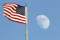 The moon rises past the U.S. flag at the Rangers Ballpark in Arlington, Saturday, July  28, 2012.(Tom Fox/Staff Photographer)