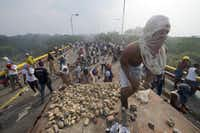 TOPSHOT - Demonstrators throw stones after a truck was set on fire at the Francisco de Paula Santander international bridge Bridge linking Cucuta, Colombia, and Urena, Venezuela, during an attempt to cross humanitarian aid over the border into Venezuela, on February 23, 2019. - US-donated humanitarian aid was