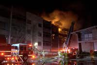 Dallas Fire-Rescue personnel fight a 7-alarm fire at the Preston Place condos in the 6200 block of West Northwest Highway early Saturday, March 4, 2017.(Metro Video)