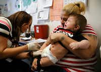 Eight-month-old Rambo Islas cries as he is held by his mother Maria Islas, who watches as nurse Nicole Ives (left), administers vaccines at the Dallas County Health & Human Services immunization clinic on Friday, March 8, 2019.(Vernon Bryant/Staff Photographer)