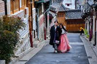 Tourists tread lightly and whisper when visiting Bukchon Hanok Folk Village in Seoul, a neighborhood of restored homes from centuries past. Many visitors rent historical costumes to mimic the fashion of the Joseon Dynasty.(Christopher Reynolds/Los Angeles Times)