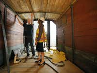Historic preservationist Ron Siebler shows Mary Pat Higgins, president and CEO of the Dallas Holocaust Museum, the latest progress on the boxcar's installation Friday in the West End. (Tom Fox/Staff Photographer)
