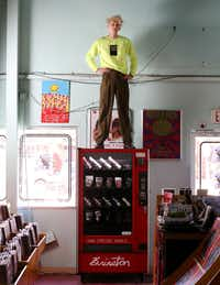 Artist Matthew Brinston poses for a photograph atop his art vending machine at Good Records in Dallas (Rose Baca/Staff Photographer)