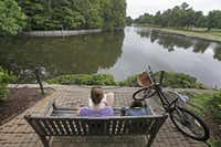 Natalie Miller enjoys a quiet moment of reading by Exall Lake in Highland Park in Dallas on Wednesday, June 25, 2014. (Louis DeLuca/Staff Photographer)