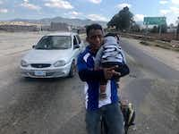Jonathan David Cardenas, 32, with 8-month-old son Julio Cesar, walked along a main thoroughfare in Guanajuato, Mexico, the week of Jan. 22, 2019. They were asking for handouts from motorists and were part of a caravan that originated in San Pedro Sula, Honduras, headed for Houston.(Alfredo Corchado/Staff Photo)