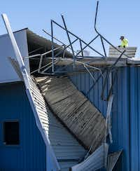 Workers clear sheet metal from the roof of Polymer Products in Grand Prairie, which suffered storm damage.(Smiley N. Pool/Staff Photographer)