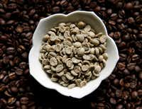 Sweet Maria's Brazil Dry Process Serrinha Yellow Bourbon green coffee beans sit on top of the same type of coffee beans after being roasted at Keith Marton's home in Dallas.(Vernon Bryant/Staff Photographer)