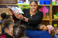 Erika Littlejohn, 3, leans on Natasha Hymes as she reads a book to the class at ChildCareGroup Martin Luther King, Jr Center on Monday.(Shaban Athuman/Staff Photographer)