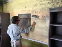 Artist Ken Conner paints mold on the walls of the Flooded House Museum in New Orleans.(Kevin McGill/The Associated Press)