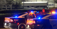 A Red Bird man and his 3-year-old son get inside a police car after an accidental shooting involving the toddler and his brother.(Metro Video Services)
