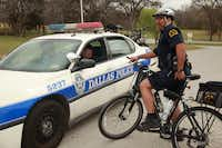 Dallas police officers Juan Amaya (on bike) and Scot Jenkins talked during a patrol  around White Rock Lake in March 2011.(File Photo/Staff)