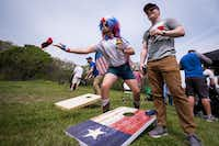Fans Clayton Ferrell (center) and Ryan Handy play cornhole as they tailgate before the Texas Rangers Opening Day game against the Chicago Cubs at Globe Life Park on Thursday, March 28, 2019, in Arlington. (Smiley N. Pool/The Dallas Morning News)(Smiley N. Pool/Staff Photographer)