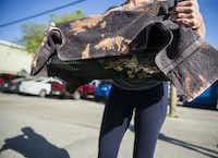 """Catsnips team member Robyn carries a captured cat to a vehicle at an apartment complex near Cedar Springs Road. """"For us to come today and get three is good,"""" Robyn said.(Daniel Carde/Staff Photographer)"""