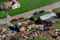 In this March 29, 2000 file photo, a house on the west side of Fort Worth, Texas, sits undamaged while homes across the street were severely damaged by a tornado that hit the area. Insurance Council of Texas records show the tornado that killed two people in Fort Worth was the 21st costliest storm in state history.(Donna McWilliam/AP)