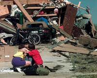 In this March 29, 2000 file photo, Tracy-Lynn Clough-Rian, center, gets a hug from her neighbors Theresa Smith and Preston Smith, 9, in front of Tracy-Lynn's tornado-destroyed home in Arlington, Texas.(LM Otero/AP)