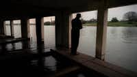 A long-ago photo of a man fishing from the old White Rock Lake boathouse on the T&P Hill..(Louis DeLuca/Staff photp)