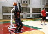 Toyota's basketball robot Cue 3 demonstrates Monday, April 1, 2019 at a gymnasium in Fuchu, Tokyo. The 207-centimeter (six-foot-10) -tall machine made five of eight three-pointer shots in a demonstration in a Tokyo suburb Monday, a ratio its engineers say is worse than usual. Toyota Motor Corp.'s robot, called Cue 3, computes as a three-dimensional image where the basket is, using sensors on its torso, and adjusts motors inside its arm and knees to give the shot the right angle and propulsion for a swish.(AP Photo/Yuri Kageyama)(Yuri Kageyama/AP)