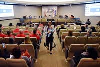 Candace Valenzuela, 34, of Dallas, with her baby, Jacinto Baldwin, walks back to her seat after discussing why she's in favor of a paid parental leave program for city employees in DeSoto.(Ben Torres/Special Contributor)