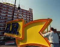 Designer Don Beck helped steady part of the neon sign that would read South Side on Lamar in 2000.(File Photo/The Dallas Morning News)