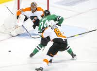 Philadelphia Flyers goaltender Cam Talbot (33) gets help from his teammate defenseman Robert Hagg (8) as Dallas Stars left wing Roope Hintz (24) takes a shot during the third period of an NHL hockey game at American Airlines Center in Dallas on Tuesday, April 2, 2019. (Shaban Athuman/Staff Photographer)