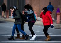 Girls walk in to the the wind as they cross S Griffin St on Saturday, January 19, 2019 in downtown Dallas.(Ashley Landis/Staff Photographer)
