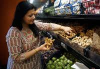 Sapna Punjabi-Gupta grabs some turmeric root while shopping at the India Bazaar in Irving.(Lawrence Jenkins/Special Contributor)
