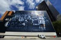 """A young man stands by a 68-by-193-foot mural of Dallas Mavericks forward Dirk Nowitzki before driving away from the YMCA building in downtown Dallas on March 24, 2019. The Mavericks say it's an augmented reality wall where """"Dirk comes to life on your smartphone with 21 shots from all 21 of his historic seasons."""" The <g class=""""gr_ gr_7 gr-alert gr_spell gr_inline_cards gr_disable_anim_appear ContextualSpelling"""" id=""""7"""" data-gr-id=""""7"""">wallscape&nbsp;</g>will be active through April 13.&nbsp;(Tom Fox/Staff Photographer)"""