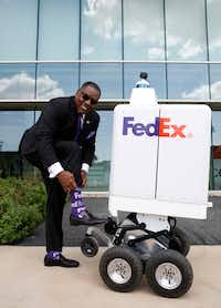 Mayor of Plano Harry LaRosiliere shows off his FedEx socks during a demonstration for the FedEx same-day bot outside the FedEx Office headquarters in Plano. He said the bot could help the city fight congestion by taking cars and trucks off the road.(Rose Baca/Staff Photographer)