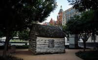 A replica of John Neely Bryan Cabin is pictured in Founders Plaza on Elm Street in downtown Dallas. The Old Red Courthouse rises above the cabin. (Tom Fox/Staff Photographer)
