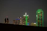 The downtown skyline lights up behind walkers on the Trinity Skyline Trail on Thursday, April 4, 2019, in Dallas.(Smiley N. Pool/Staff Photographer)