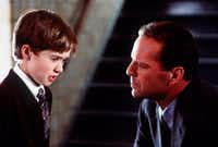 Haley Joel Osment (left) and Bruce Willis starred in <i>The Sixth Sense</i>, the 1999 debut from writer-director M. Night Shyamalan.&nbsp;(Ron Phillips/Spyglass Entertainment)