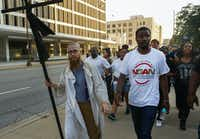 """The Rev. Dr. Jeff Hood, left, and Dominique Alexander lead protestors east on Commerce St during the """"Finish the March: A Defiance of Fear"""" event on Thursday July 6, 2017. The protestors gathered at the Old Red Museum to finish last year's anti-police brutality march that was cut short by the Dallas Police ambush.(Ron Baselice/Staff Photographer)"""