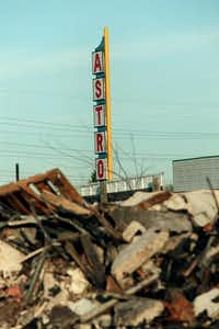 The Astro Drive-In sign towers over rubble  after the old drive-in movie theater was torn down in 1999.(Staff/The Dallas Morning News)