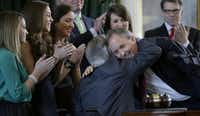 Ken Paxton (right) embraced Gov.-elect Greg Abbott after Paxton was sworn in as Texas attorney general in January 2015.(File Photo/The Associated Press)