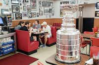 The Stanley Cup sits on a table at Norma's Cafe in Dallas as patrons eat lunch. The Keeper of the Stanley Cup, Howie Borrow, was in Dallas visiting local TV stations and other media with the trophy.(Tommy Noel/Staff Photographer)