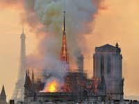 With the Eiffel Tower in the distance, flames and smoke rise from the blaze at Notre Dame Cathedral in Paris that destroyed its spire and its roof but spared its twin medieval bell towers, and prompted a frantic rescue effort to save its most precious artifacts.(Thierry Mallet/AP)