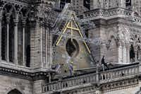 Workers install protective tarps on the roof of  Notre Dame cathedral in Paris on April 23, 2019, one week after a fire devastated the cathedral.(Christophe Archambault/AFP/Getty Images)