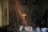 Smoke rises around the altar in front of the cross inside Notre Dame Cathedral as debris from the roof continues to burn on the floor on April 16, 2019(Philippe Wojazer/AFP/Getty Images)
