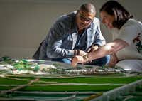 Darren James, a Trinity Park Conservatory board member, left, listens while Elizabeth Silver, a member of the design team, talks while looking at a model of Harold Simmons Park on display at Old Dallas High School in Dallas, Texas on April 25, 2019.(Robert W. Hart/Special Contributor)