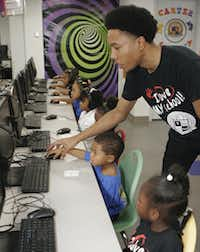 Technology instructor Andrew Carter worked with students last fall in the computer lab at Inspiring Body of Christ's school, the University of Dreams.(Milton Hinnant/Milton Hinnant/Special Contribut)