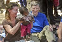 Melinda Gates and her husband, Microsoft founder Bill Gates, play with a child in Jamsot Village near Patna, India.(2011 File Photo/The Associated Press)