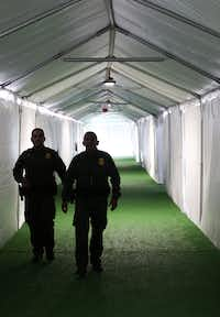 U.S. Border Patrol agents walk the hallway of a temporary holding facility near the Donna-Rio Bravo International Bridge on Thursday, May 2, 2019 in Donna, Texas. Officials say the soft-sided tent facility will primarily be used as a temporary site for processing and care of asylum seekers crossing the border and will increase the Border Patrol's capacity to process migrant families while they await transfer to U.S. Immigration and Customs Enforcement or to the Department of Health and Human Services. (Ryan Michalesko/The Dallas Morning News)(Ryan Michalesko/Staff Photographer)