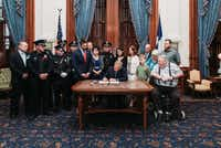 Gov. Greg Abbott, surrounded by Richardson-area lawmakers, and David Sherrard's parents, Margaret and Alvin, signs into law a bill that would rename parts of the North Central Expressway after the fallen police officer.