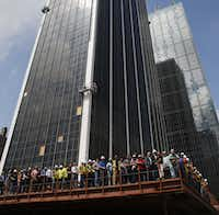 Construction workers pose for a photograph as renovation restarts at First National Bank Tower in downtown Dallas.(Rose Baca/Staff Photographer)